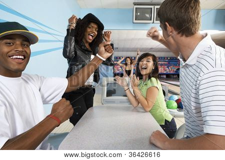 Multiethnic friends cheering at bowling alley