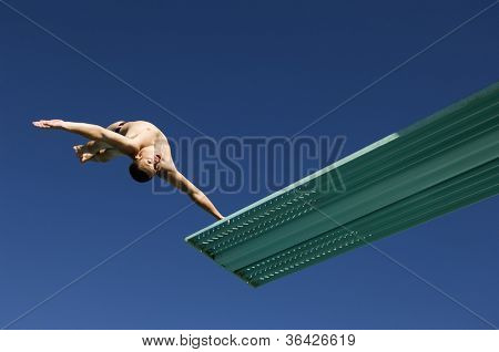 Low angle view of a male diver diving backwards in midair