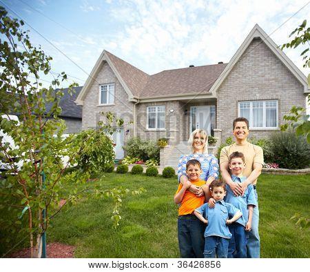 Familia feliz junto a la nueva casa. Concepto de bienes raíces.