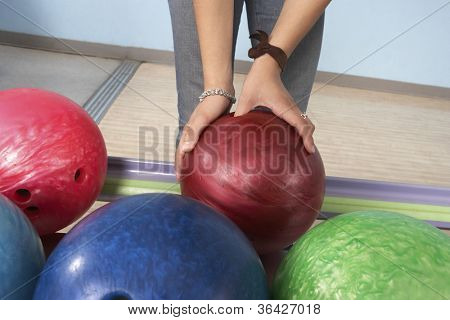 Woman at bowling alley choosing ball