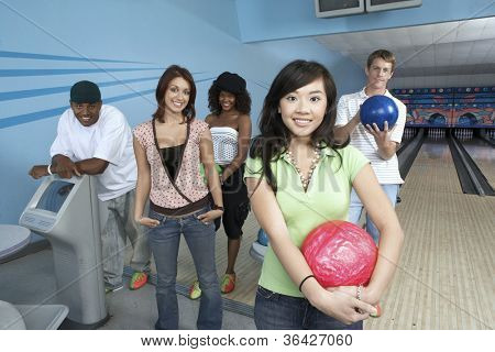 Group portrait of happy multiethnic friends at bowling alley
