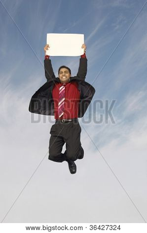 Cheerful businessman holding a blank placard while jumping