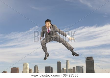 Full length of a cheerful Chinese businessman in midair