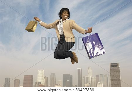 Cheerful senior businesswoman jumping in midair with shopping bags