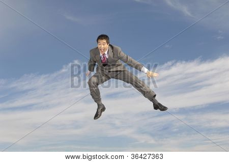 Full length of a businessman in midair shouting against cloudy sky
