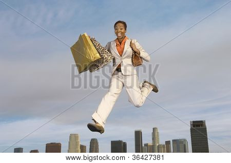 Portrait of an ecstatic businesswoman with shopping bags in midair