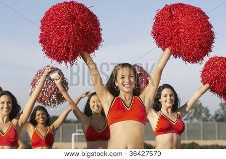 Group of happy multiethnic cheerleaders cheering with pompom