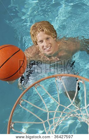 Young man playing water basketball in swimming pool