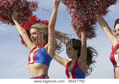 Cheerleaders running together with pompoms against clear sky