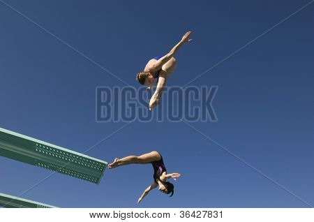 Low angle view of two female divers diving in midair against clear sky