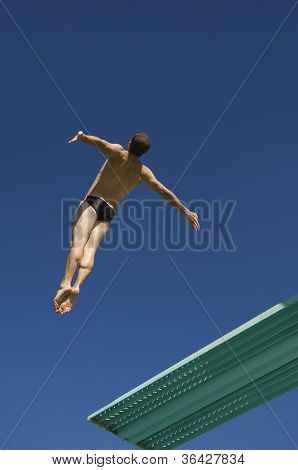 Low angle view of a male diver diving from springboard in midair