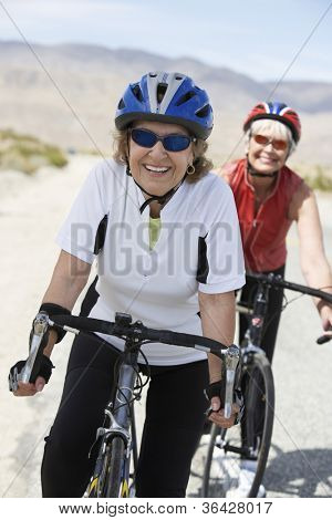 Senior female friends riding bicycle