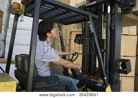 Man driving forklift from side