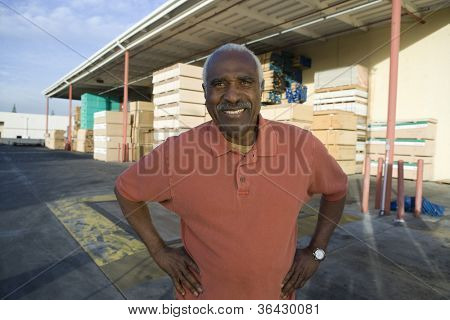Portrait of a confident senior man with hands akimbo at warehouse