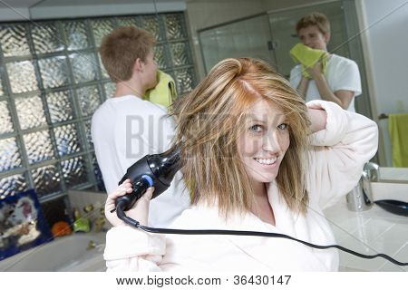 Portrait of woman drying her hair with man in bathroom