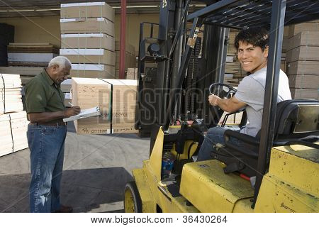 Male worker driving fork truck and senior man writing on the clipboard