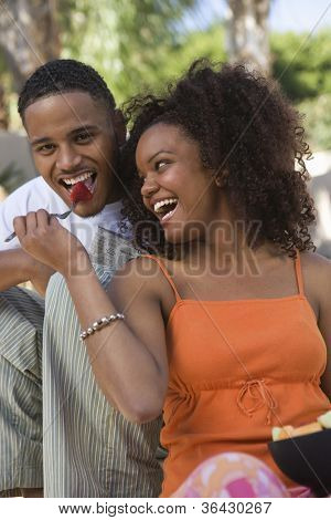 Cheerful young African American couple eating fruit salad
