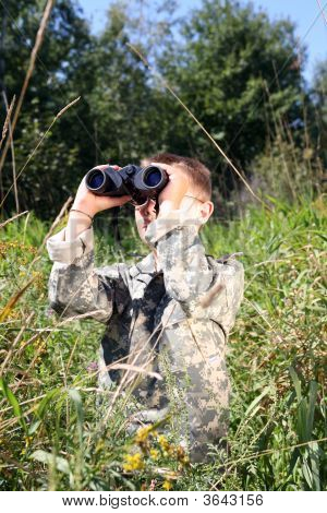 Young Boy In Field Looking Up Through Binoculars