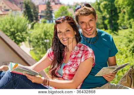 Young happy couple on vacation with map smiling travel tourists