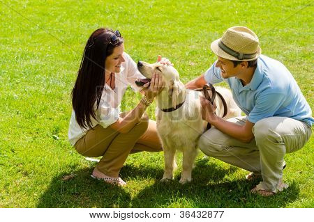 Young happy couple playing with Labrador dog smiling in park
