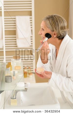 Senior woman apply make-up powder in front of bathroom mirror
