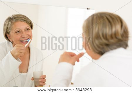 Mature woman brushing teeth with toothpaste looking in bathroom mirror