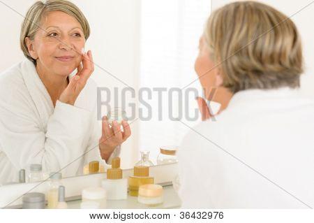 Senior woman looking in bathroom mirror applying anti-wrinkles face cream
