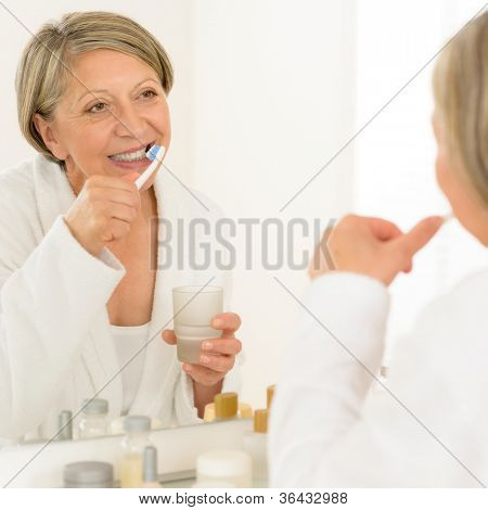 Senior woman brushing teeth looking at herself in bathroom mirror