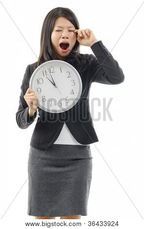 Tired Asian business woman holding a clock and rubbing eye, isolated on white background.
