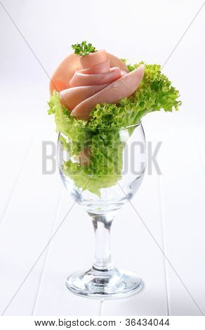 Fresh ham and salad rose in a wine glass