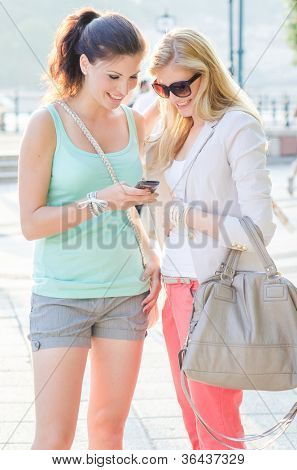 Two happy female friends looking on mobile phone