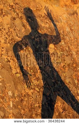 woman shadow on granite rock under warm sunset light