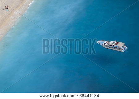 Boat On The Ionic Sea, A Romantic Couple At The Beach