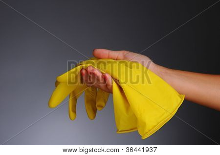 Closeup of a womans hand holding a pair of yellow rubber gloves over a light to dark gray background.