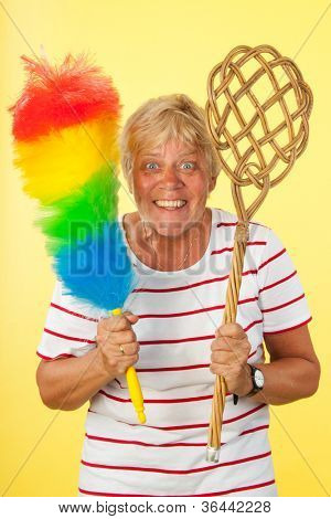 Mad housewife with carpet beater and feather broom