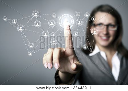 Businesswoman in suit pressing social media icon