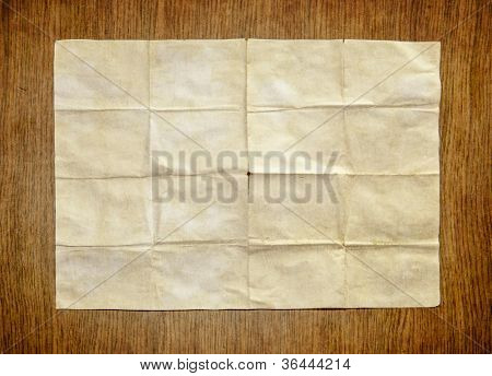 Old white paper sheet on wooden table