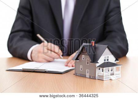 Immobilien-Konzept - Vertrag Geschäftsmann Zeichen hinter Hause Architekturmodell