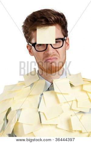 Unhappy young man with a sticky note on his face, covered with stickers, isolated on white