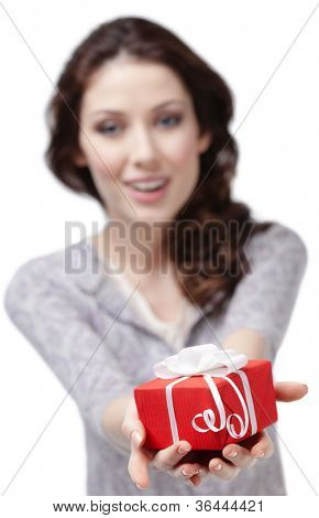 Young woman offers a present wrapped in red paper, isolated on white