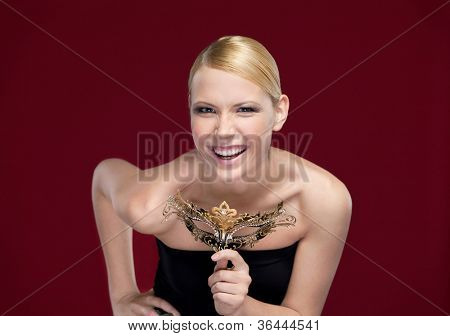 Pretty girl with patterned masquerade mask, isolated on purple