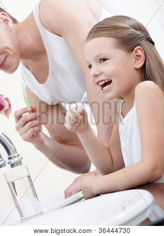 Little girl brushes her teeth with her father in bathroom