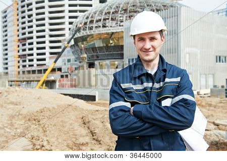 One happy engineer builder foreman with blueprint plan working drawing at construction site