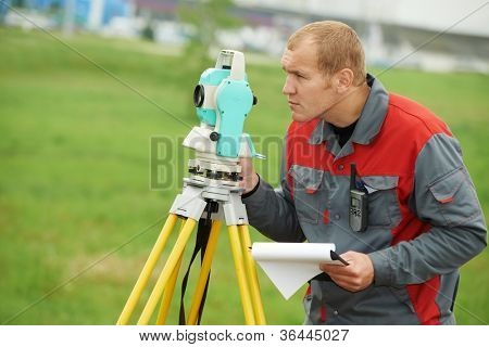 One surveyor worker working with theodolite transit equipment at spring field construction site outdoors
