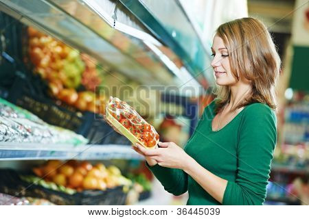 woman choosing apple during shopping at fruit vegetable supermarket