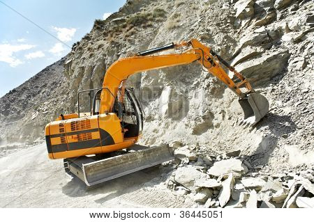 track-type loader excavator machine doing earthmoving roadwork at mountain