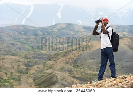 One tourist traveller hiker with binoculars in Himalayas mountains