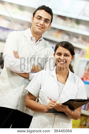 Two cheerful pharmacist chemist woman and man standing in pharmacy drugstore