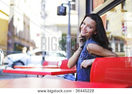 beautiful young woman sitting alone in street cafe