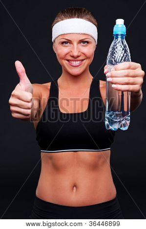 sporty female holding water and showing thumbs up